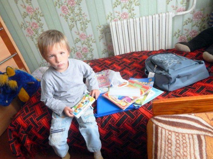 Мальчик сидит на кровати, рядом — книжки и канцтовары
