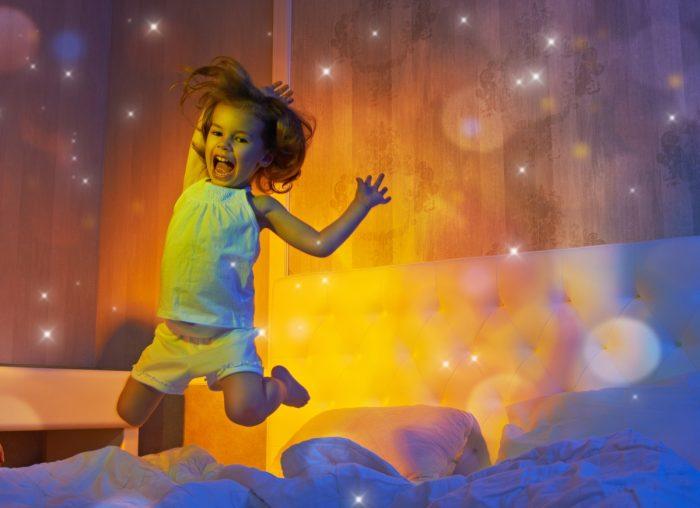 Девочка вечером прыгает по кровати