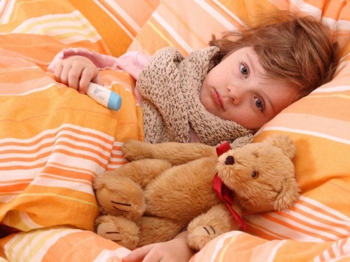 Ребёнок, укутанный шарфом, лежит в постели с плюшевым мишкой