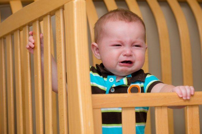 Младенец стоит в своей кроватке и плачет