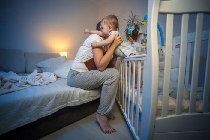 Мама обнимает ребёнка, его кроватка стоит рядом с постелью взрослых