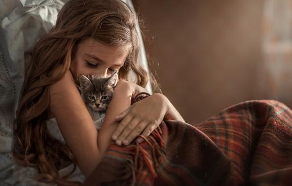 Девочка лежит в кровати с котёнком
