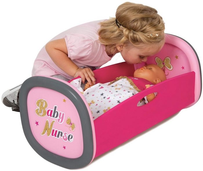 Девочка укладывает спать игрушечного грудного младенца