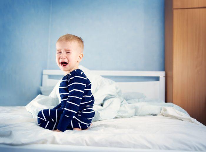 малыш на кровати плачет