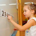 На доске выложены цифры от 0 до 10, девочка показывает пальцем на цифру 4