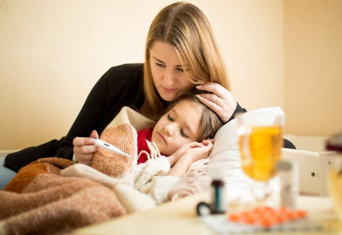 Девочка закутана в плед, мама обнимает её и смотрит на термометр, на столе лекарства