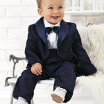 Мальчик в костюме сидит на диване