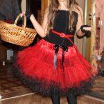 На девочке одета пышная юбка, на голове бейсболка, в руках корзина