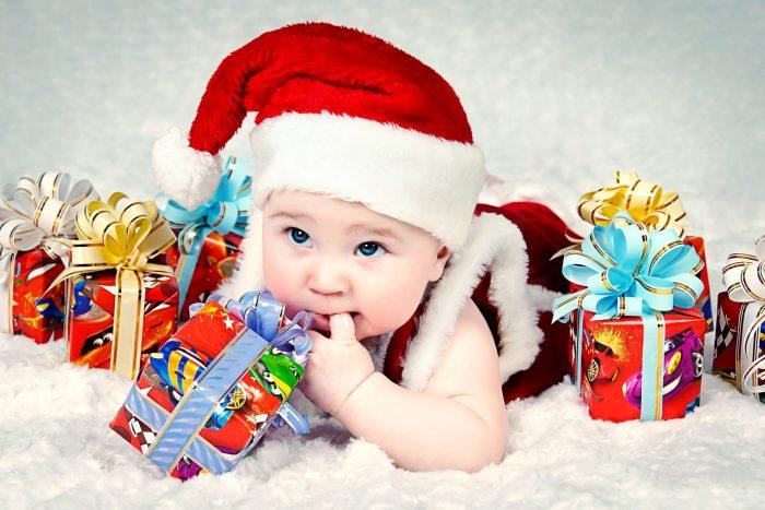 Малыш в шапке Деда Мороза среди подарков