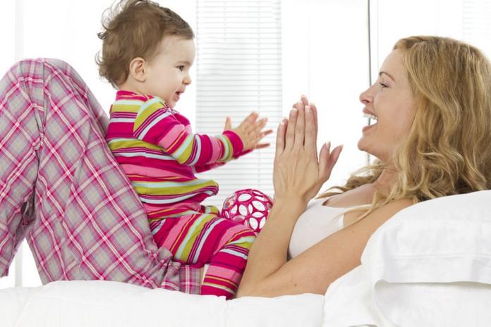 Мама лежит на кровати с грудным ребёнком, играет с ним в ладошки и разговаривае