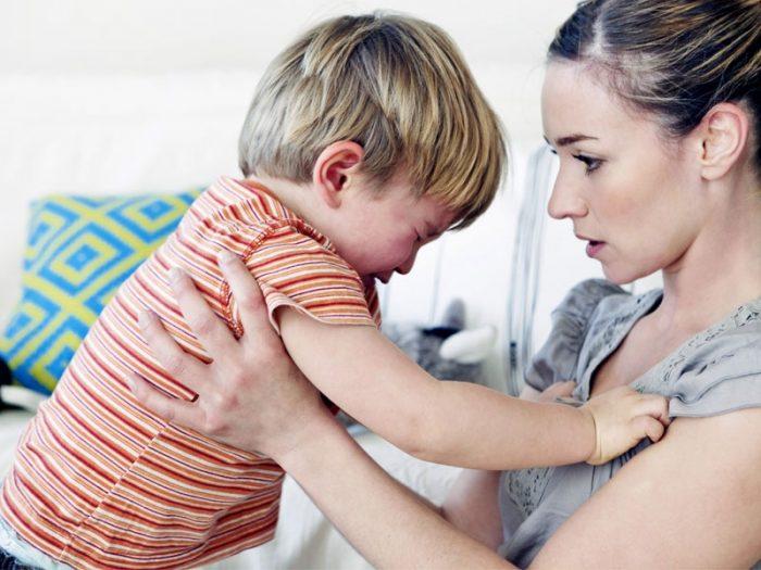 Недовольный мальчик плачет, мама держит его