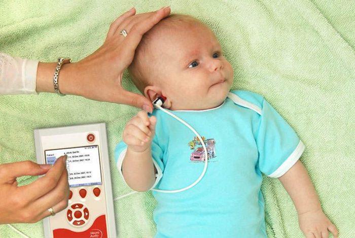 Младенцу проверяют слух специальным аппаратом