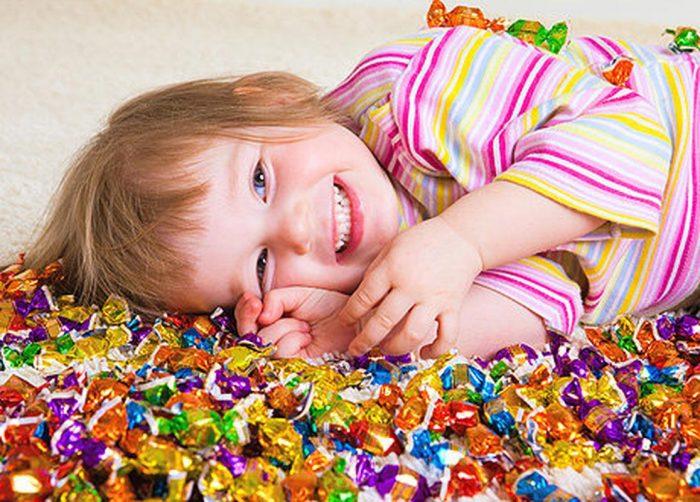 Девочек лежит среди конфет