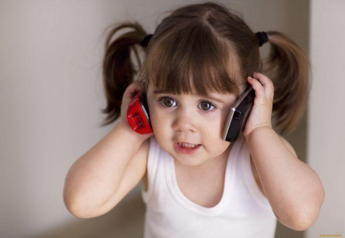 Маленькая девочка разговаривает сразу по двум телефонам