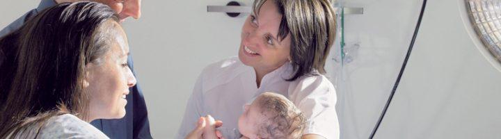 Пара смотрит на ребёнка после совместных родов