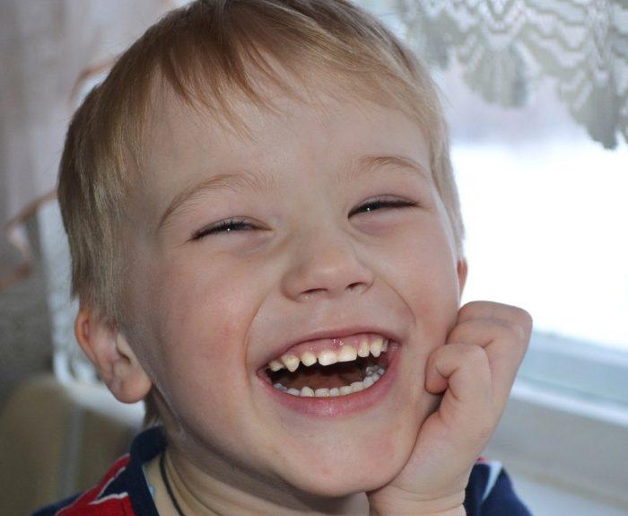 Мальчик широко улыбается