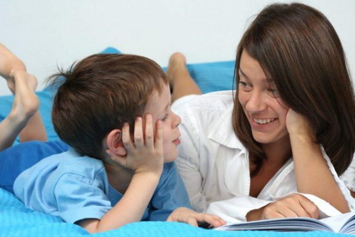 Мама смотрит на сына и улыбается (оба лежат на кровати)