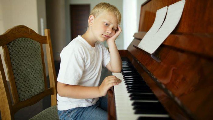ребенок сидит у фортепиано
