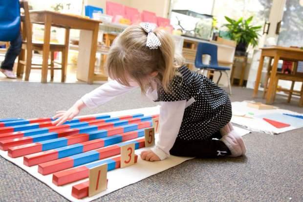 Девочка играет с цветными брусками