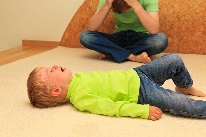 Трёхлетний мальчик лежит на полу и плачет, на заднем плане папа взялся за голову