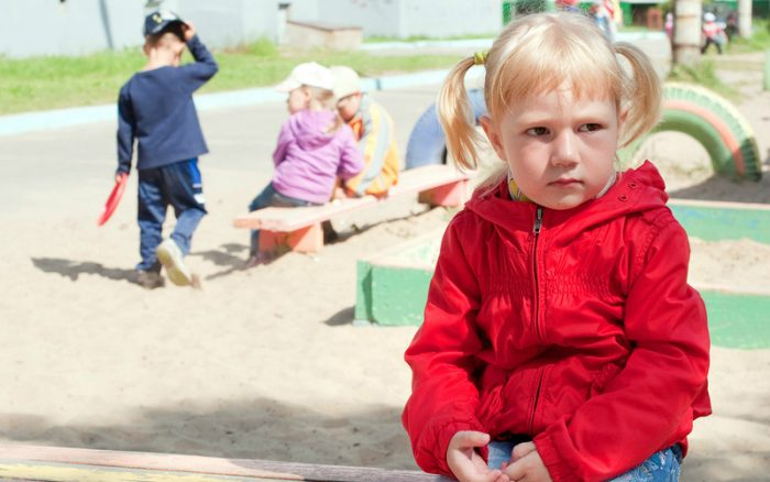 Девочка сидит недовольная в стороне от играющих детей
