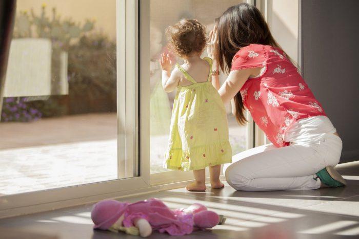 Мама с маленькой дочкой смотрят в окно