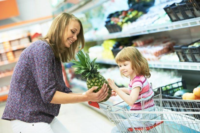 Мама показывает девочке ананас в супермаркете