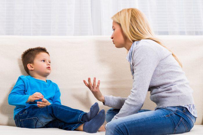 Мама что-то объясняет мальчику, оба сидят на диване