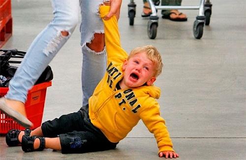 Мальчик сидит на полу и плачет в магазине, мама тащит его за руку