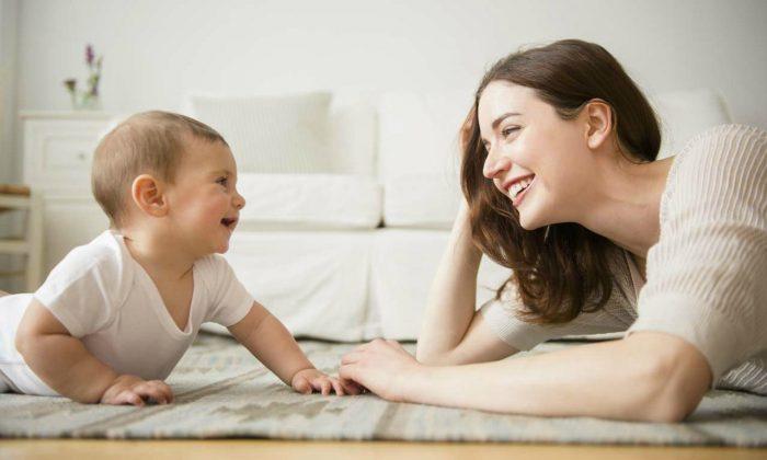 Мама разговаривает с годовалым малышом, оба лежат на полу и смотрят друг на друга