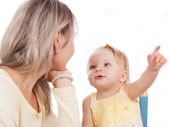 Девочка указывает на что-то пальчиком, смотрит на маму и говорит