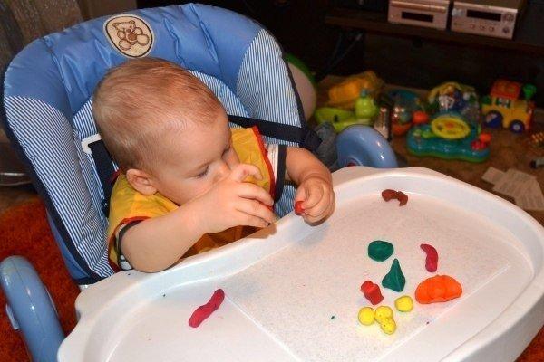 Годовалый малыш, сидя за детским столиком, занимается с пластилином