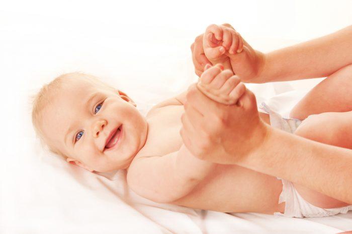 Мама держит за руки младенца, лежащего на спине