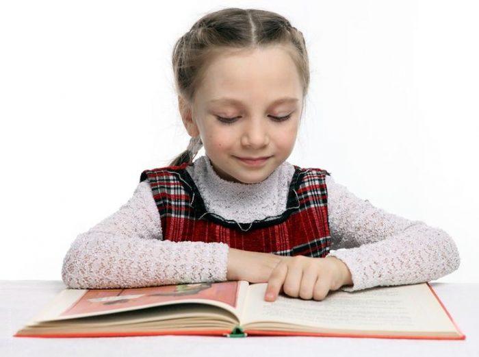 Девочка сосредоточенно читает книгу, проводя пальцем по тексту