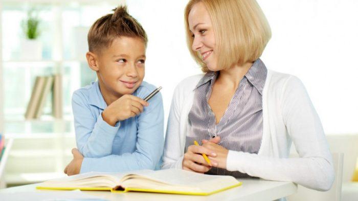 Мальчик сидит с мамой за книгой и показывает на неё указкой