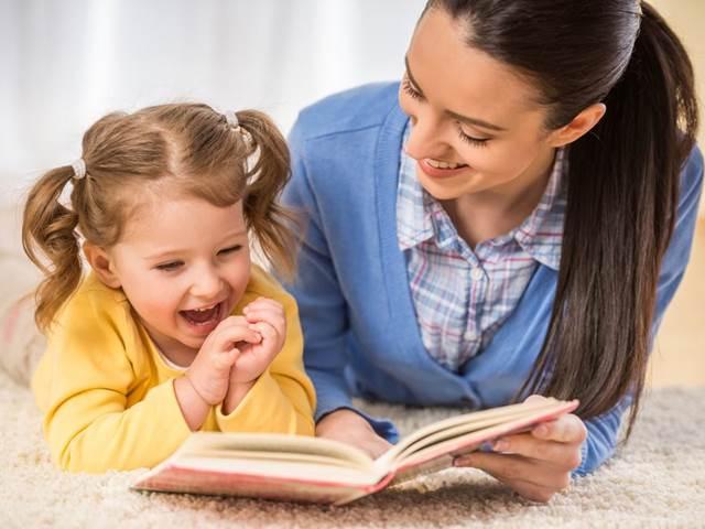 Мама с дочкой-дошкольницей читают книгу