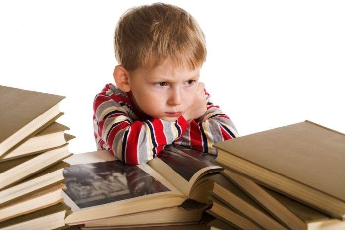 Недовольный мальчик сидит рядом со стопками книг