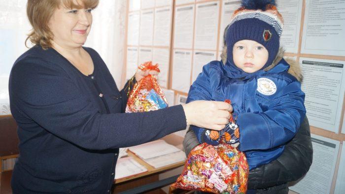 Сотрудница Фонда социальной защиты вручает ребёнку новогодний подарок