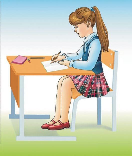 Девочка правильно сидит за столом во время письма