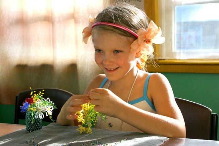 Девочка мастерит поделку из бисера