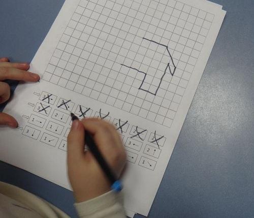 Ребёнок рисует по клеточкам
