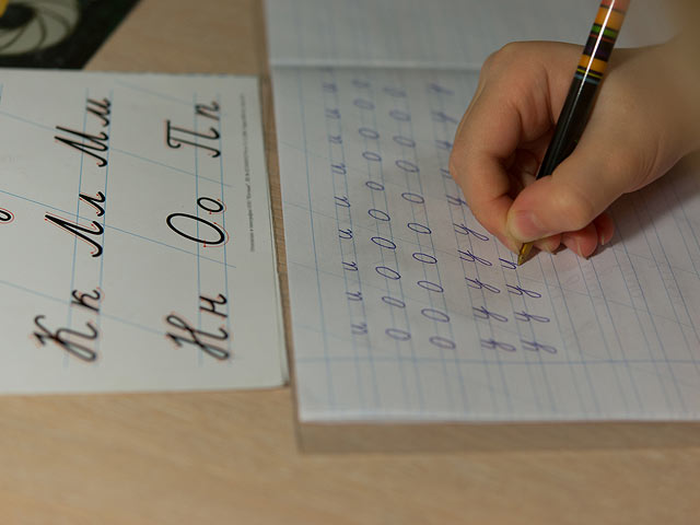 Ребёнок пишет буквы в тетради