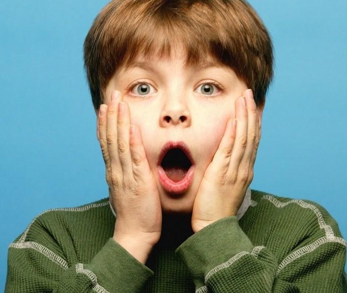 Мальчик раскрыл рот от удивления и обхватил щёки руками