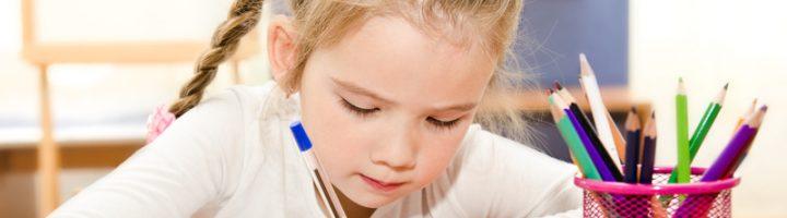 Девочка пишет ручкой в тетради