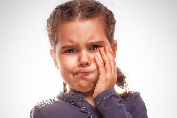Девочка держится за щёку — у неё болит зуб