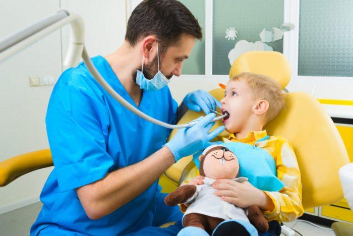 Врач лечит зубы мальчику, у того в руках мягкая игрушка