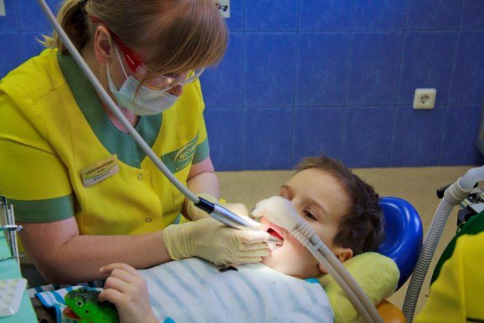 Мальчик в креле стоматолога, на его носу находится маска, через которую поступает газ
