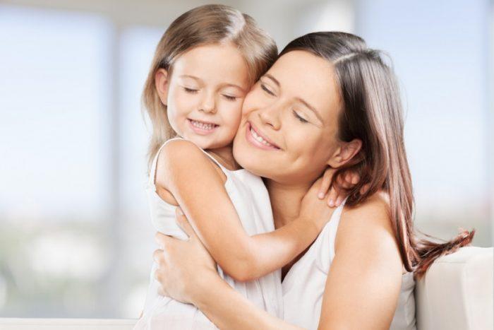 Мама обнимает дочку и улыбается