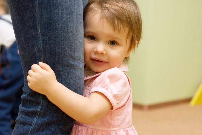 Девочка держится за ногу взрослого