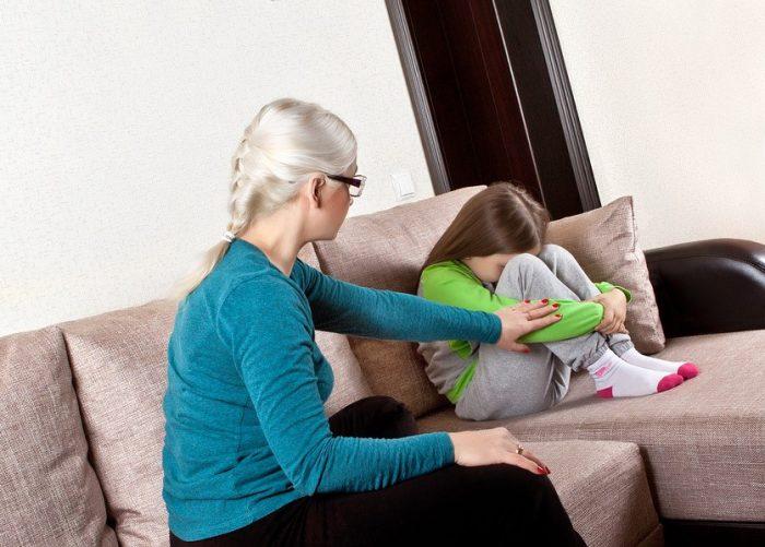 Девочка сидит на диване, уткнувшись в колени и переживает, мама её успокаивает